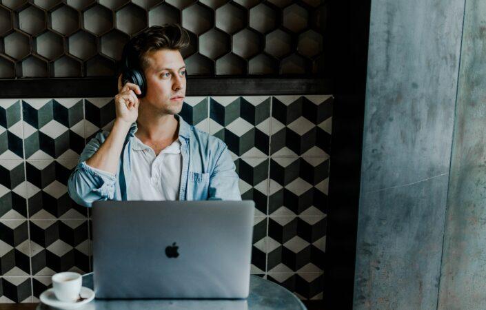 Man achter laptop luistert muziek